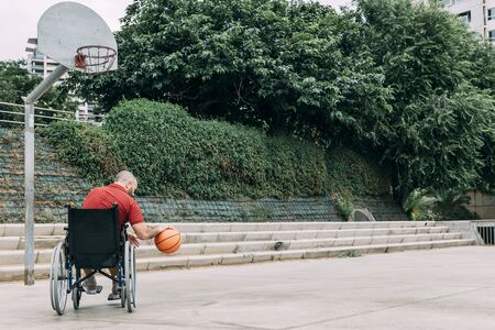 disabled man in wheelchair playing on basket on the basketball court alone, concept of adaptive sports and physical activity, rehabilitation for people with physical disabilities