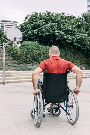 disabled man in wheelchair playing basketball on the court, concept of adaptive sports and physical activity, rehabilitation for people with physical disabilities, vertical photo