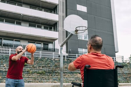 joyful disabled man in wheelchair playing basketball with a friend with a ball, concept of adaptive sports and physical activity, rehabilitation for people with physical disabilities