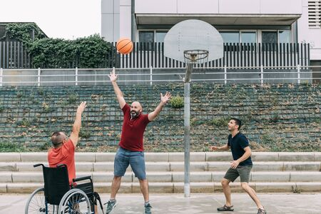 joyful disabled man in wheelchair throwing the ball to basket with friends, concept of adaptive sports and physical activity, rehabilitation for people with physical disabilities 写真素材