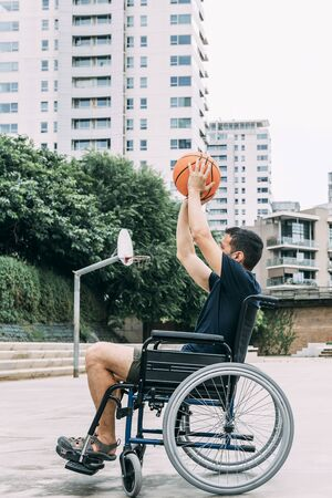 disabled man in wheelchair throwing ball to basket alone, concept of adaptive sports and physical activity, rehabilitation for people with physical disabilities, vertical photo