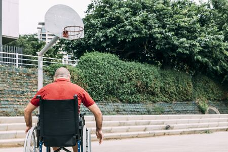 disabled man in wheelchair on the basketball court alone, concept of adaptive sports and physical activity, rehabilitation for people with physical disabilities 写真素材