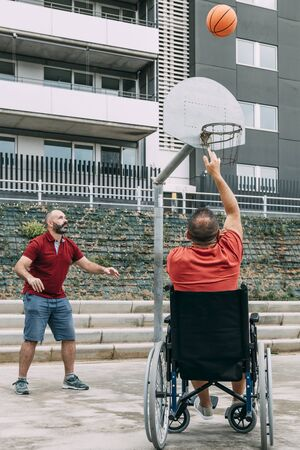 joyful handicapped man in wheelchair throwing the ball to basket with a friend, concept of adaptive sports and physical activity, rehabilitation for people with physical disabilities, vertical photo 写真素材