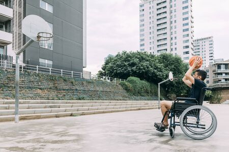 handicapped man in wheelchair playing basketball alone, concept of adaptive sports and physical activity, rehabilitation for people with physical disabilities 写真素材