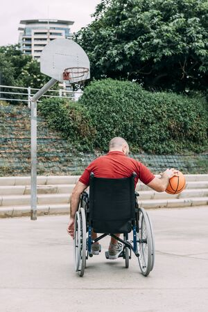 disabled man in wheelchair playing basketball alone in the city, concept of adaptive sports and physical activity, rehabilitation for people with physical disabilities, vertical photo 写真素材
