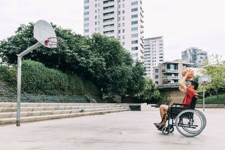 handicapped man in wheelchair throwing ball to basket alone, concept of adaptive sports and physical activity, rehabilitation for people with physical disabilities 写真素材