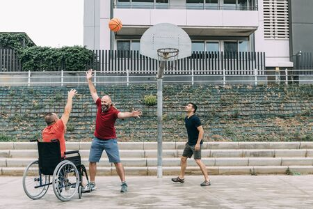 joyful disabled man in wheelchair playing basketball with two friends with a ball, concept of adaptive sports and physical activity, rehabilitation for people with physical disabilities