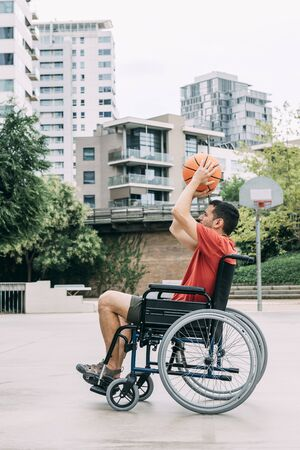 handicapped man in wheelchair playing basketball alone in the city, concept of adaptive sports and physical activity, rehabilitation for people with physical disabilities, vertical photo 写真素材