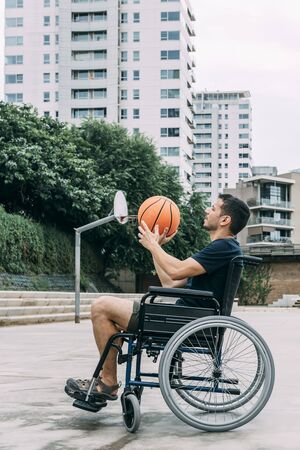 disabled man in wheelchair playing basketball alone, concept of adaptive sports and physical activity, rehabilitation for people with physical disabilities, vertical photo