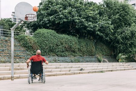 handicapped man in wheelchair playing on basket on the basketball court alone, concept of adaptive sports and physical activity, rehabilitation for people with physical disabilities 写真素材