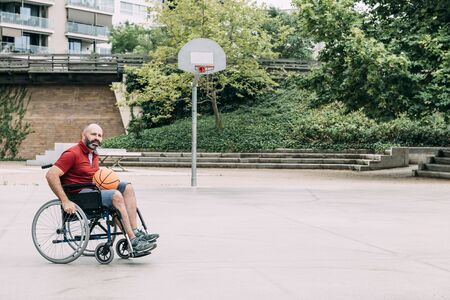 disabled man in wheelchair playing on basketball court alone, concept of adaptive sports and physical activity, rehabilitation for people with physical disabilities