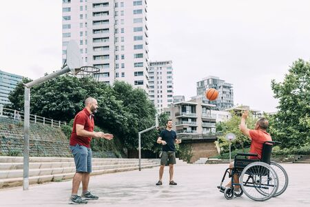 joyful disabled man in wheelchair playing with a basket ball with friends, concept of adaptive sports and physical activity, rehabilitation for people with physical disabilities 写真素材