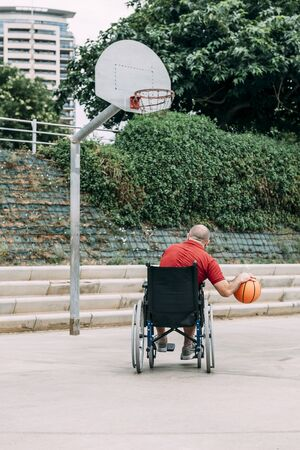 man in wheelchair playing basketball alone in the city, concept of adaptive sports and physical activity, rehabilitation for people with physical disabilities, vertical photo