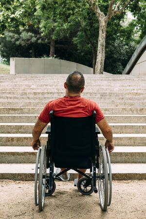 vertical photo of a disabled man on wheelchair stopped in front of stairs who cant climb looking up for help, raising awareness of accessibility issues for people with reduced mobility 写真素材