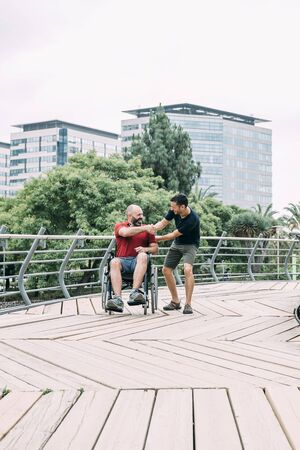 disabled man in wheelchair shake hands with his friend during a walk at park at city, concept of friendship and integration of people with disabilities and reduced mobility problems, vertical photo Stockfoto