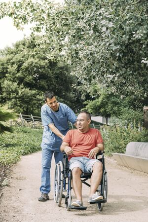 disabled man in wheelchair talking during a walk with his nurse at park, concept of medical care and rehabilitation of people with disabilities and reduced mobility problems, vertical photo