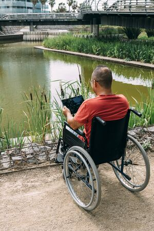 disabled man in wheelchair having fun while working using a tablet computer at park, concept of technological and occupational integration of people with disabilities and reduced mobility problems