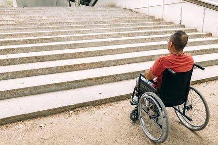Behinderte im Rollstuhl hielten vor Treppen, die nicht klettern können, um Hilfe zu suchen, um das Bewusstsein für architektonische Barrieren und Zugänglichkeitsprobleme für Menschen mit eingeschränkter Mobilität zu schärfen