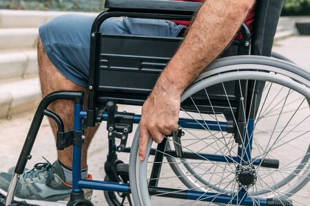 Close up of disabled man sitting in a wheelchair, his hand is holding the wheel, raising awareness of accessibility issues for people with reduced mobility Stockfoto