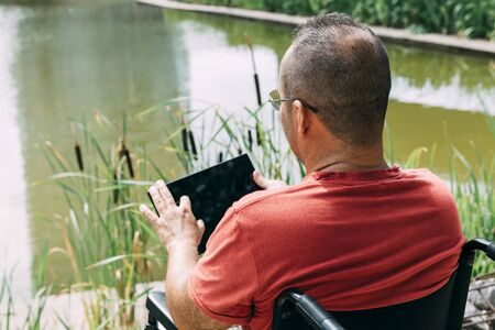 handicapped man in wheelchair having fun while resting using a tablet computer at park, concept of technological and occupational integration of people with disabilities and reduced mobility problems