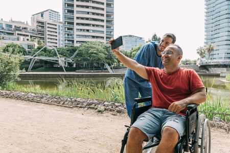 disabled man in a wheelchair taking a photo with his caretaker during a walk, concept of medical care and rehabilitation of people with disabilities and reduced mobility problems Stockfoto