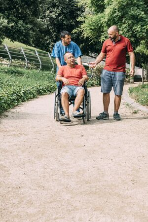 disabled man in a wheelchair talking with his caretaker and a friend at park, concept of medical care and rehabilitation of people with disabilities and reduced mobility problems, vertical photo