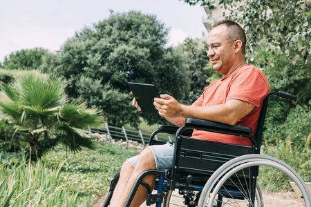 disabled man in wheelchair having fun while working at park using a tablet computer, concept of technological and occupational integration of people with disabilities and reduced mobility problems