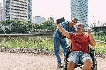 disabled man in a wheelchair taking a selfie with his caretaker during a walk, concept of medical care and rehabilitation of people with disabilities and reduced mobility problems