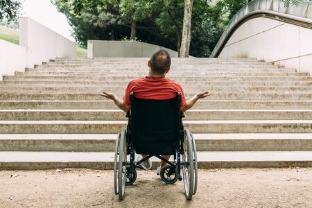 disabled man on wheelchair stopped outraged in front of stairs who can't climb looking for help, raising awareness of architectural barriers and accessibility issues for people with reduced mobility Archivio Fotografico - 128724101