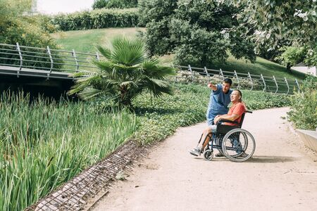 caretaker talking with his disabled patient in a wheelchair during a walk, concept of medical care and rehabilitation of people with disabilities and reduced mobility problems Фото со стока - 128724102