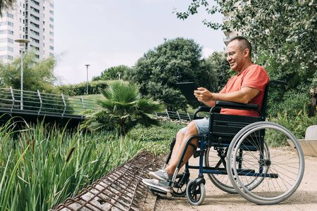 handicapped man in wheelchair having fun while working using a tablet computer at park, concept of technological and occupational integration of people with disabilities and reduced mobility problems 写真素材
