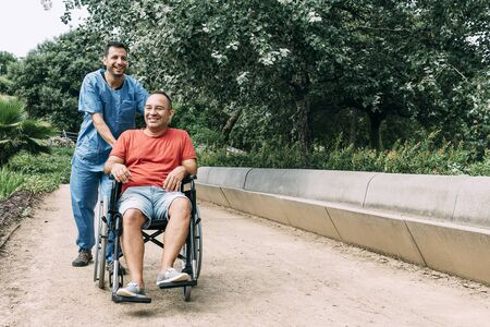 disabled man in wheelchair laughing during a walk with his nurse at park, concept of medical care and rehabilitation of people with disabilities and reduced mobility problems