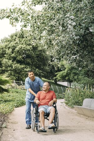 disabled man in wheelchair talking during a walk with his caretaker at park, concept of medical care and rehabilitation of people with disabilities and reduced mobility problems, vertical photo Stockfoto