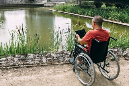 disabled man in wheelchair having fun while resting using a tablet computer at park, concept of technological and occupational integration of people with disabilities and reduced mobility problems