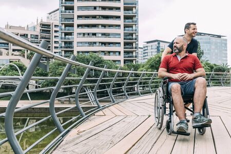 disabled man in wheelchair converses with his friend during a walk, concept of friendship and integration of people with disabilities and reduced mobility problems, vertical photo Фото со стока