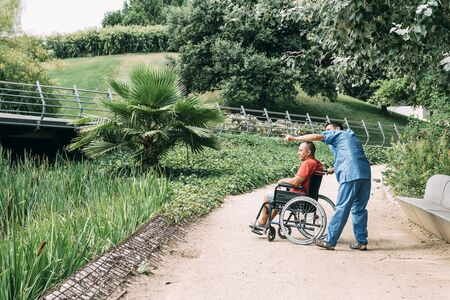 disabled man in a wheelchair talking with his caretaker during a walk, concept of medical care and rehabilitation of people with disabilities and reduced mobility problems Stockfoto