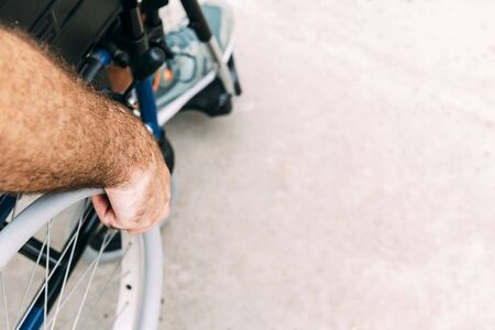 Close up of disabled man sitting in a wheelchair, he holds his hand on the wheel, raising awareness of accessibility issues for people with reduced mobility Фото со стока