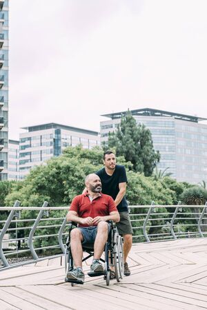 disabled man in wheelchair walks with his friend through the city, concept of friendship and integration of people with disabilities and reduced mobility problems, vertical photo