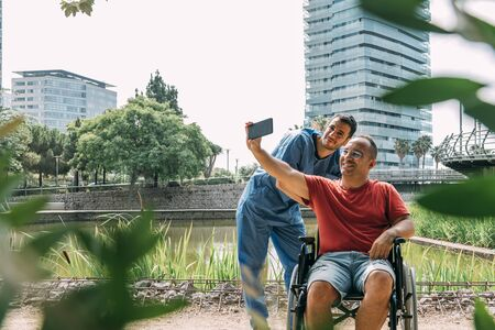 disabled man in a wheelchair taking a picture with his caretaker during a walk, concept of medical care and rehabilitation of people with disabilities and reduced mobility problems