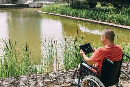 disabled man in wheelchair having fun while resting looking a tablet computer at park, concept of technological and occupational integration of people with disabilities and reduced mobility problems
