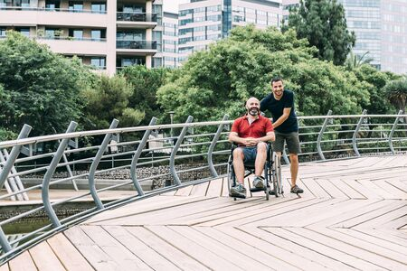 disabled man in wheelchair walking and laughing in the park with a friend, concept of friendship and integration of people with disabilities and reduced mobility problems