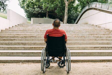Hombre discapacitado en silla de ruedas parado frente a escaleras que no pueden subir buscando ayuda, creando conciencia sobre problemas de accesibilidad para personas con movilidad reducida.
