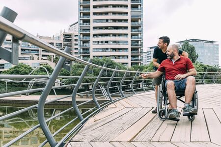 disabled man in a wheelchair talking to his friend during a walk, concept of friendship and integration of people with disabilities and reduced mobility problems, vertical photo