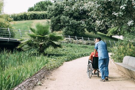 man pushes his disabled patients wheelchair into the park, concept of medical care and rehabilitation of people with disabilities and reduced mobility problems Stockfoto