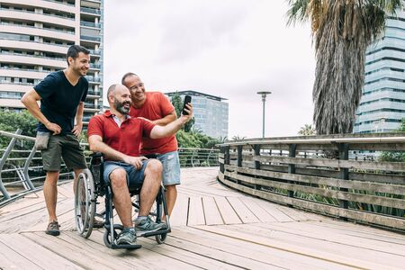 disabled man in wheelchair taking a selfie with his phone with two friends during a walk, concept of friendship and integration of people with disabilities and reduced mobility problems