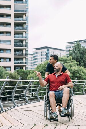 disabled man in wheelchair conversing with his friend during a walk, concept of friendship and integration of people with disabilities and reduced mobility problems, vertical photo Фото со стока