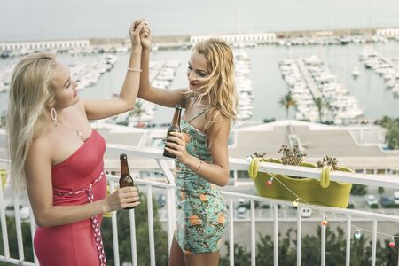 carefree young girls with beers dancing and having fun at a private party on the outdoor terrace in front of the port, leisure happiness and friendship concept