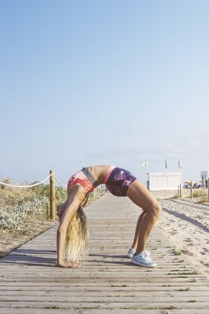 female athlete stretching and doing yoga exercises, sporty blonde girl doing warm up workout at promenade before training and running, fitness and healthy lifestyle concept, vertical photo, copy space