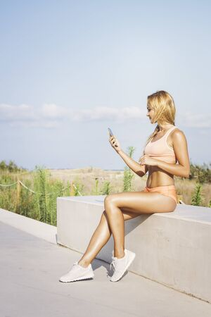 attractive female athlete looking at the phone before training, athletic sport girl consulting the app after running, technology fitness and healthy lifestyle concept, vertical photo, copy space