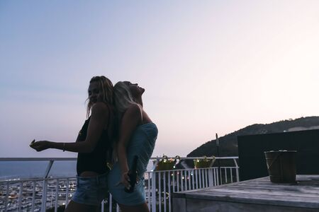 silhouette of two beautiful young girls with beers dancing and having fun at a private party on the outdoor terrace at the night, leisure happiness and friendship concept, vintage look with grain